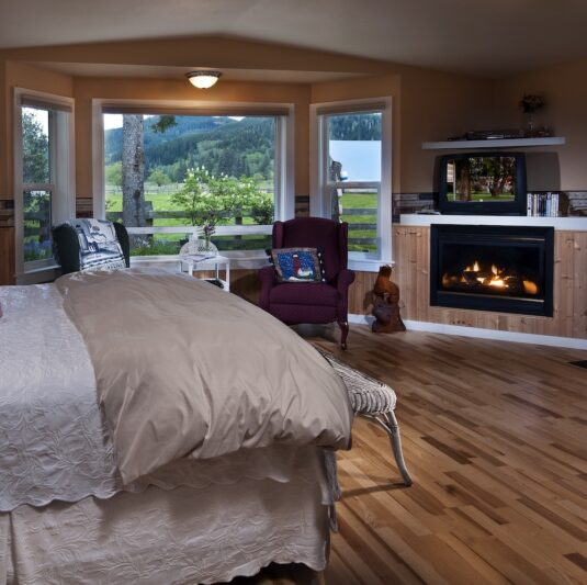 bedroom with white and off-white linens, blazing fireplace, 2 chairs set in bay window
