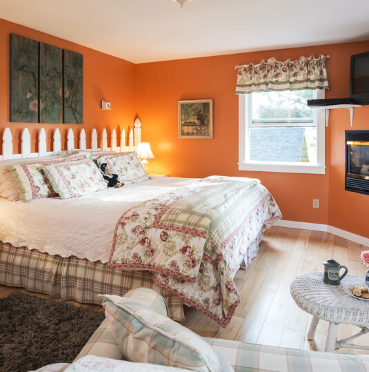 bedroom with orange walls, white fencing as headboard, fireplace set in wall