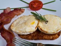 2 eggs on top of potato patty with bacon