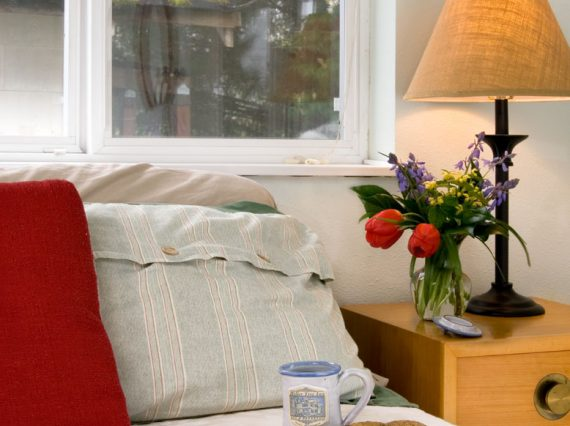 bed with red pillow and lamp on nightstand