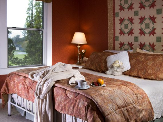 bedroom with bed with red and white linens, quilt on wall