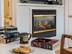 blazing fireplace behind table with books, coffee mug and cookies