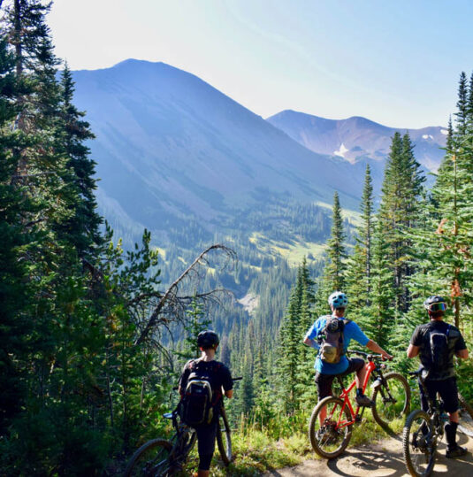 3 people riding bikes on trail overlooking mountains