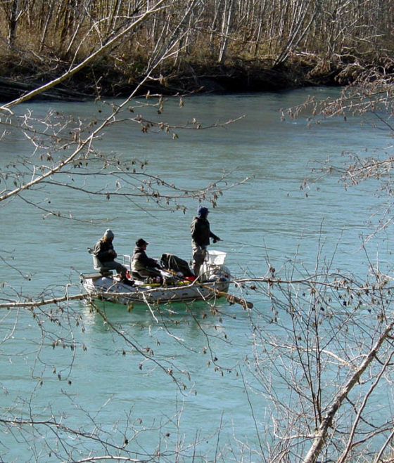 3 people in boat in river, one fishing in Mike Gurling National Park