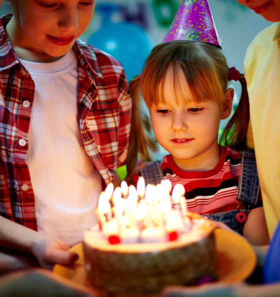 children looking at cake lit with candles