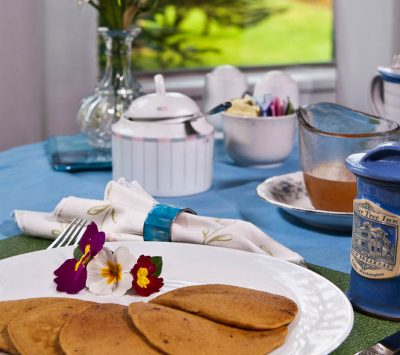 pancakes on white plate with flowers for decoration