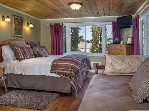 Cedar Creek Room with sofa and bed with striped linens